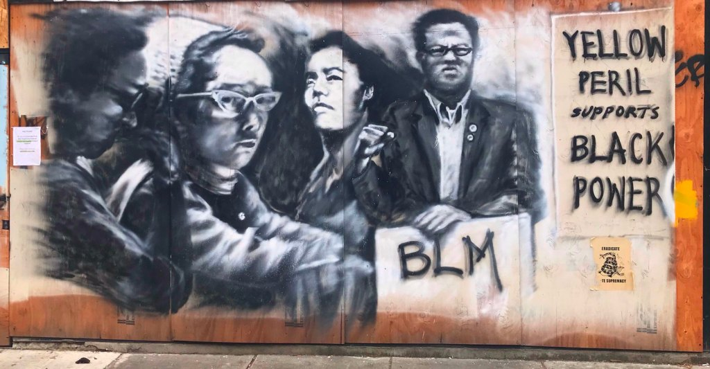 street art portraying figures and slogans about Black-Asian solidarity