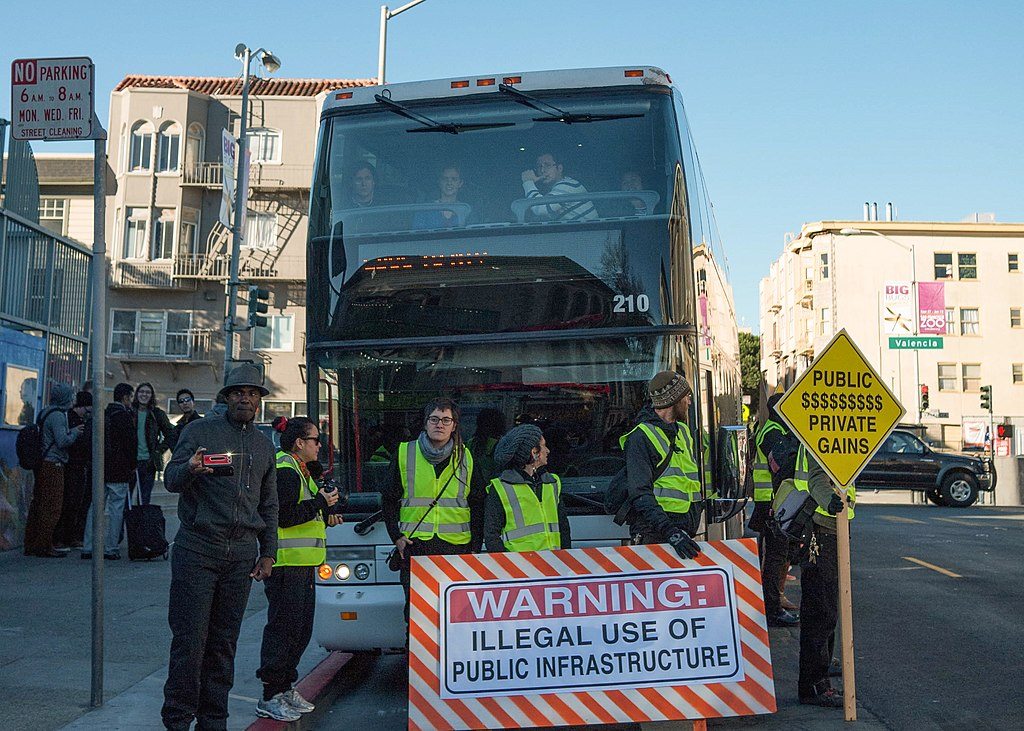 """People in yellow traffic vests stand in front of a bus with a sign that reads """"Warning: illegal use of public infrastructure."""""""