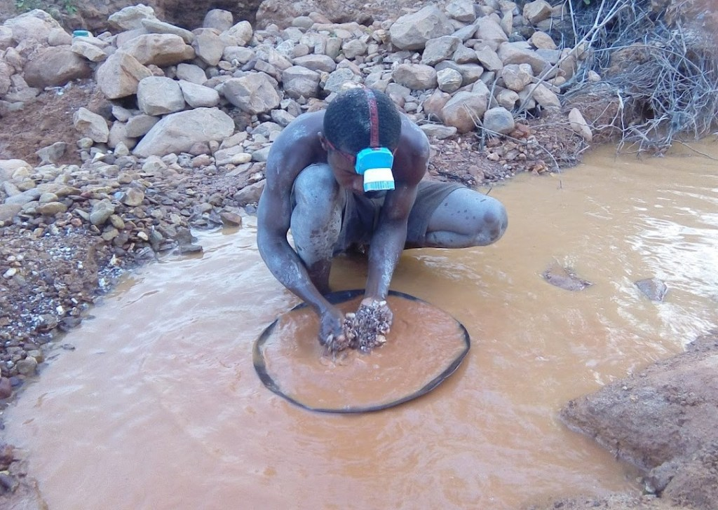 Gold miner using hands to sift through gold in murky water