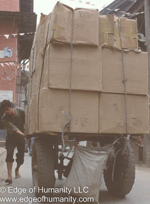 India - Man Transporting a very large load of boxes manually using a cart.