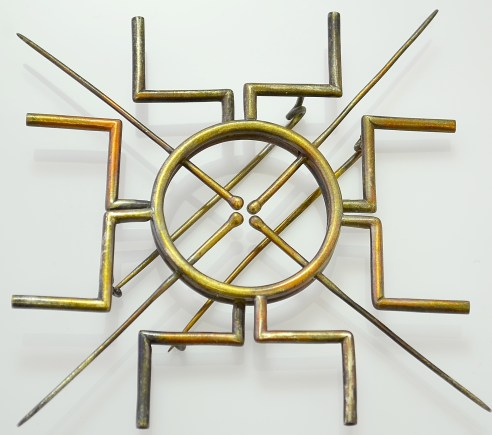 The brooch is inspired from a generalized concept of the mandala using the square and the circle. The corners of the square symbolize the 4 gates or directions: north, south, east and west. They lead to the inert, complete and pure circle, and thence to its core, led to by the 4 needles. The gates are made of hollow pipes symbolizing other passages prevalent, that may not lead to the desired destination.