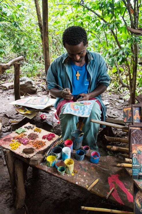This young man is painting religious pictures for sale as well as restoring the colorful artworks at the nearby church - Zeghie Peninsula, Lake Tana, in Western Ethiopia