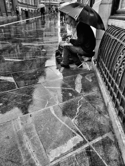 Copova Street, Ljubljana A flower vender on central Čopova Street is forced to take a break by a brief downpour.