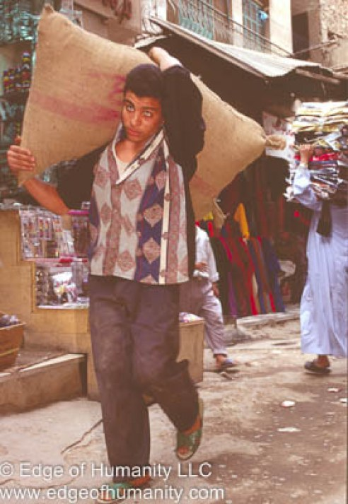 Man carrying a large sac on his shoulders - Egypt.
