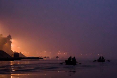The soft early pre-sunrise light on the Ganges River contrasts with the orange lights of Varanasi city.