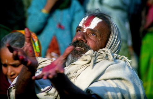 A pilgrim trying to grab a garland thrown by holymen as their blessing during Kumbh at Allahabad.