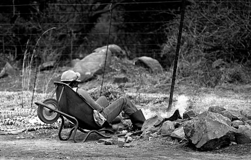 """""""The highway cowboy"""" This was an unusual sight to say the least. This is a road worker on a most probably lunch break, roadside. He was by himself and had a fire going and seemed to have dozed off in this wheel-barrow!"""