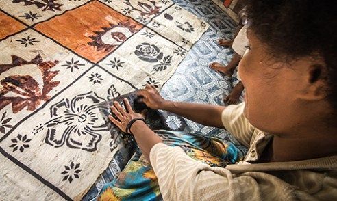 Masi: Women, men, and children gather in the community hall of Muana Village to learn the traditional art of Masi printing. Traditional designs and motifs (known as Masi) are elaborately stenciled on tapestries made from the bark of a mulberry tree.