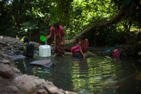 Carmelita and her daughter Maritza (11) are collecting water at a small river that flows below the rubbish dump to water their cultivations. Especially during the raining season, polluted water from the dump flows unfiltered into the river that families from Linda Vista use to wash their clothes, for personal hygiene and, when their wells dry out during dry season, even as drinking water.