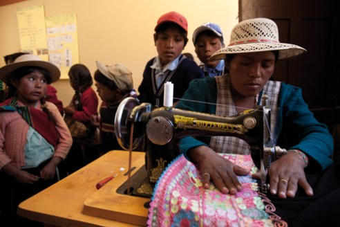 Two children watch the embroidery work of a young woman in Marcoma, Bolivia.