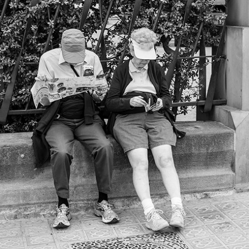 Two older people sitting on the fence of the Sagrada Familia Basilica in Barcelona.