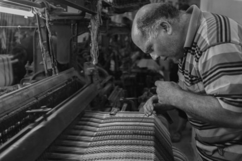 Izzat Herwabi Keffiyeh Hebron June 16, 2015 - Izzat Herbawi assists an aging loom in weaving a Keffiyeh. Herbawi continues his family business in Hebron as the the last standing keffiyeh factory in Palestine.