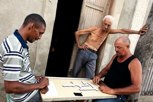 Two men playing dominoes on a street in Santiago de Cuba .