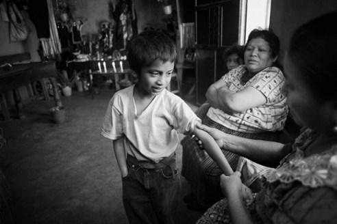 Berta Navichoc, bonesetter, treating Pedro Sicay Mendoza's broken arm. Santiago Atitlán, Guatemala