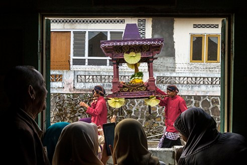 "KOPENG-INDONESIA. November 29th, 2015. Villagers watching the parade inside their home. Javanese people gather to hold a thanksgiving called ""Saparan"" to say thanks to God as their massive harvest result this year at Kopeng village, District of Semarang Central Java Indonesia. By bringing the symbol of a mountain full of food and crops they parade around the village with typical costumes and performs traditional dance."