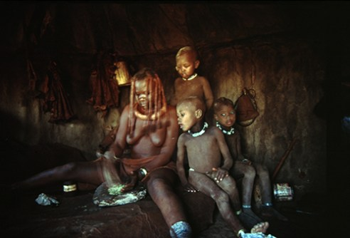Tjimbosi, Ueesiapo and Nguaarua watch as Mukaakakoye tries her hand at grinding dried perfumed plants to mix with iron oxide stone powder that with cow fat makes up the red unction women use to adorn their bodies. oHere, Kunene North Region, Namibia, 2000