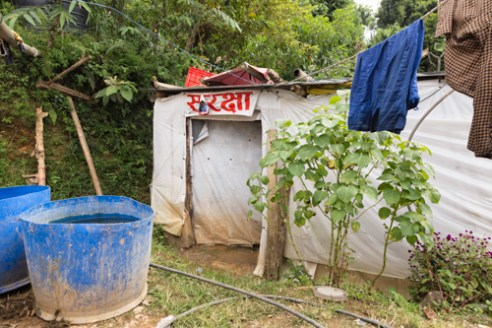 "Farmer Dilli Ram Regmi and his family are forced to reside in this temporary shelter with the word ""Safety"" printed above the entrance in Sirubari, rural Nepal. Their home was damaged and cracked as a result of the April 25th earthquake that hit the country."