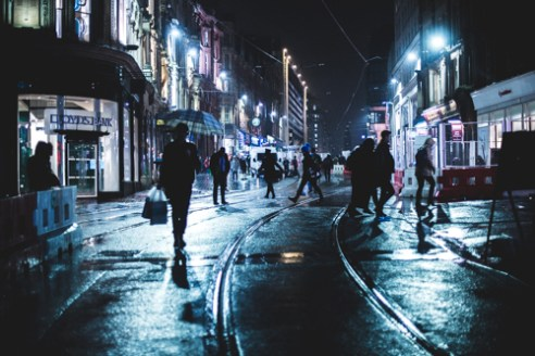 People cross paths on Corporation Street during a wet night in Birmingham