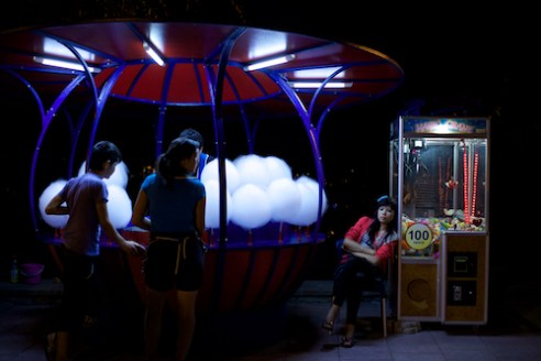 A girl sits by a candy floss machine in Kok-Tobe Amusement Park.