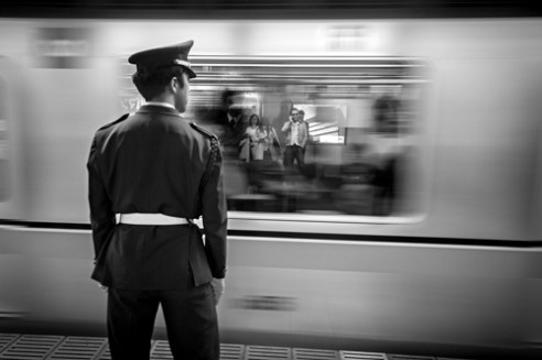 A guard keeps an eye on passengers as they wait for their train. Tokyo Metro