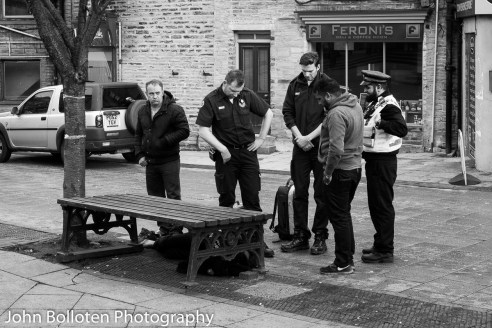 A collapsed man is watched over by medics, police and a drugs worker.