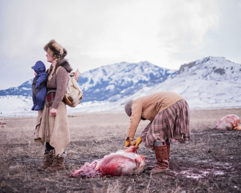 Epona waits with her backpack as Ania pulls buffalo fat from a gut pile.