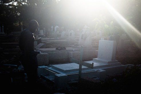 A man whitewashes a new grave in the graveyard of St Peter's Anglican Church in Lilongwe. People die young in Malawi; the WHO claims the average life expectancy for men is 57 and 60 for women.
