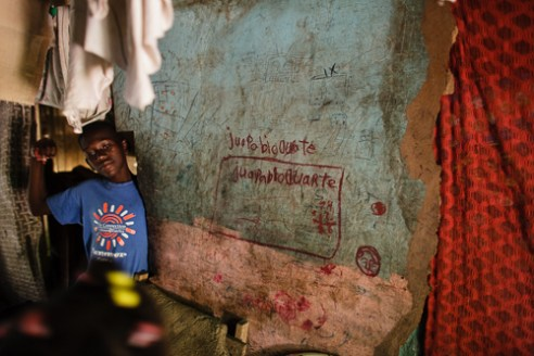 86 Young boy inside his home in a Batey near Puerto Plata. Because he is of Haitian descent he must leave school after grade seven.