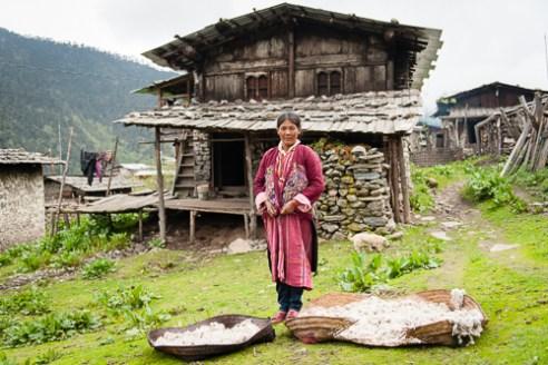 Tshewang Choden (45 yrs) drys sheep's wool outside her home in Merak.