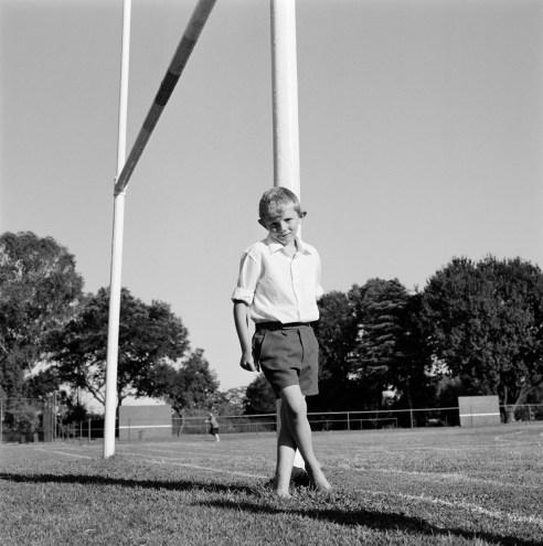 Little boy on goalpost Krugersdorp School, South Africa
