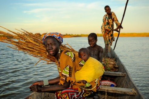 A women & her children from the Bozo tribe being taken across the Bani River. Bani River near Mopti