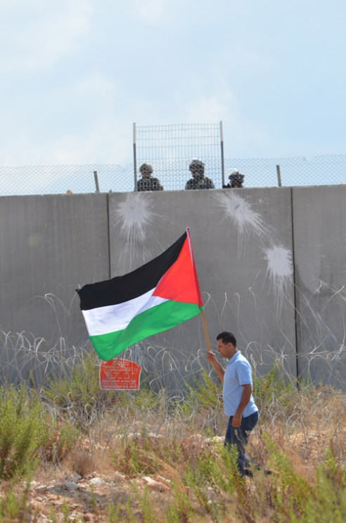 "Bil'in Palestine flag: A Palestinian protester walks beneath the well-armed Israeli soldiers in Bil'in West Bank. Holding the Palestinian flag is this man's form of peaceful protest against what he saw as the ""occupation of Palestinian land by the Israeli state""."