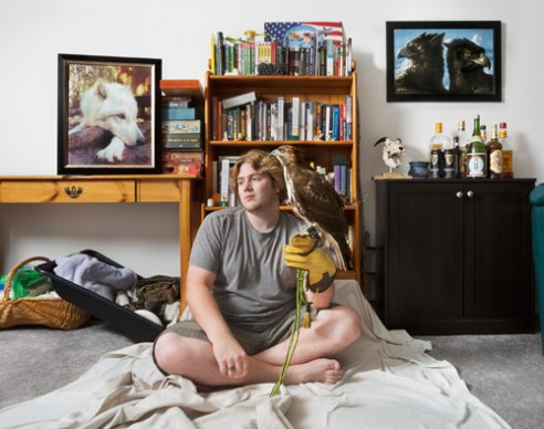 This image of the Falconer, Eric, with his Red-tailed Hawk named Tyr was made in the living room of his apartment in Debary Florida. The photograph depicts the man's everyday surroundings and the clash of domestic life with wild nature. Falconry is a complicated dance between man and bird. Falconers train juvenile birds of prey to hunt side-by-side them and after a year or two they are returned to the wild, under the provision that they have become stronger hunters. By photographing in the falconer's home I create a dynamic that captures the relationship between the domestic sphere and the world of Falconry. The attributes of the home clash unmistakably with the bird of prey, as a living fixture among the items we surround ourselves with, for comfort and entertainment. 2015.