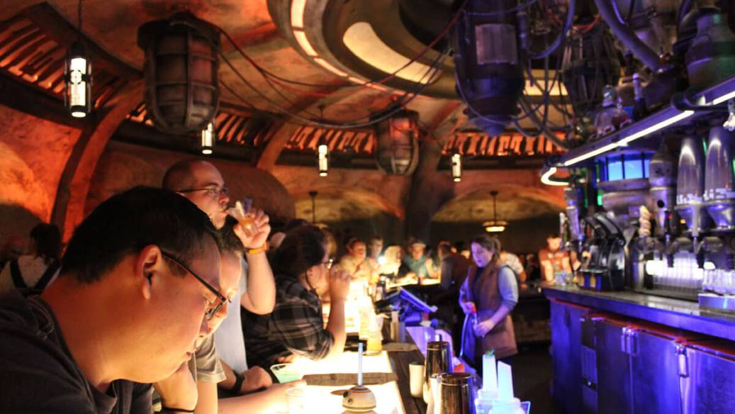 People sitting at the bar inside Oga's Cantina