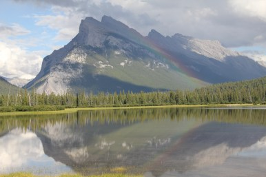 Rainbow over the mountain, reflected in the water.