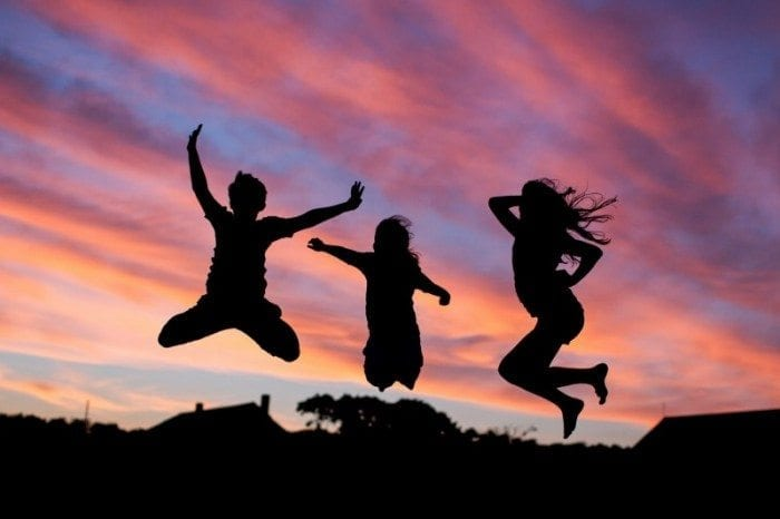 Children jumping in the air during a sunset