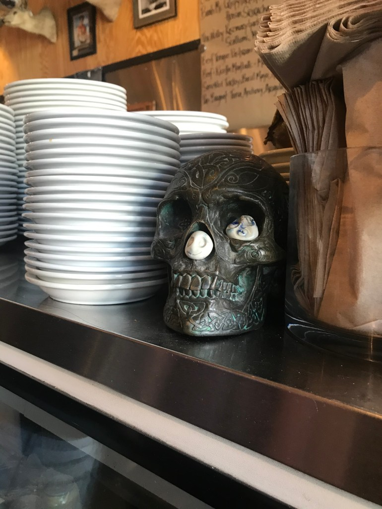 Interior picture of Industrial Eats, showing stacks of plates on the counter entrance and a patina skull.