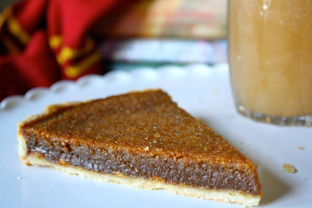 Treacle tart on plate with butter beer.