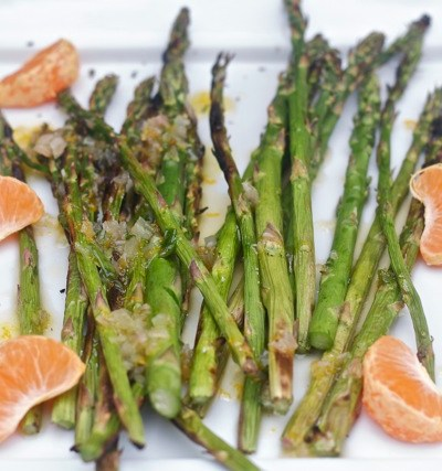 Grilled asparagus on plate with orange segments.