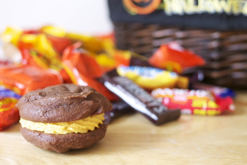 Chocolate whoopie pie with pumpkin filling, on table with Halloween candy.