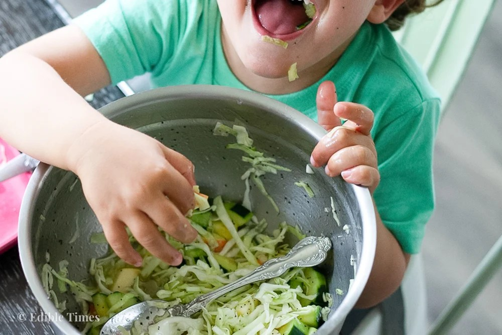 Child eating apple-cucumber slaw with poppy seed dressing.