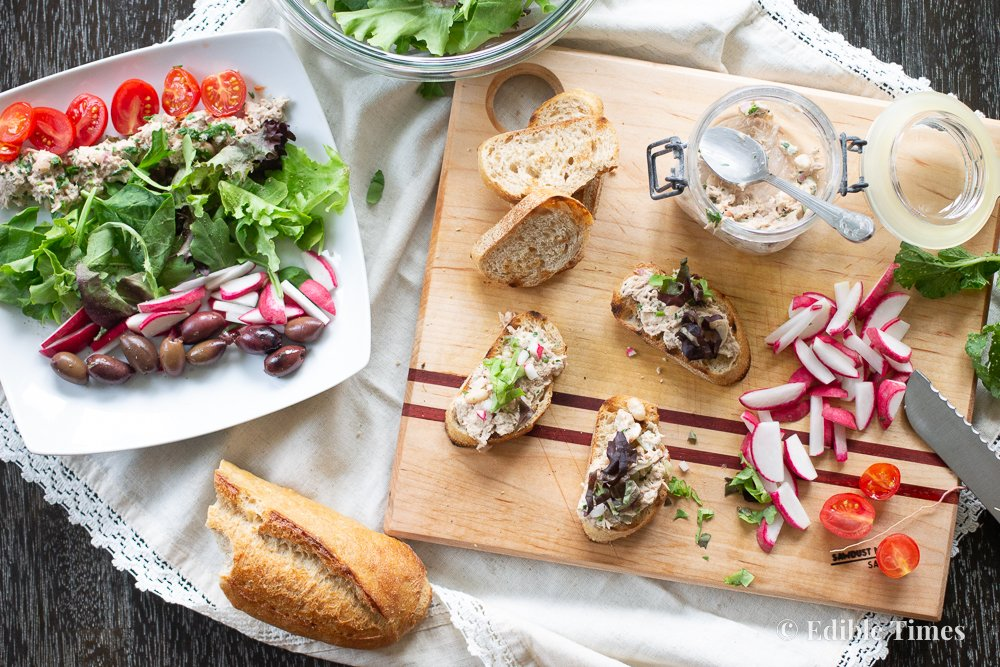 Tuna salad spread and tuna tartine on cutting board with radishes and baguette.