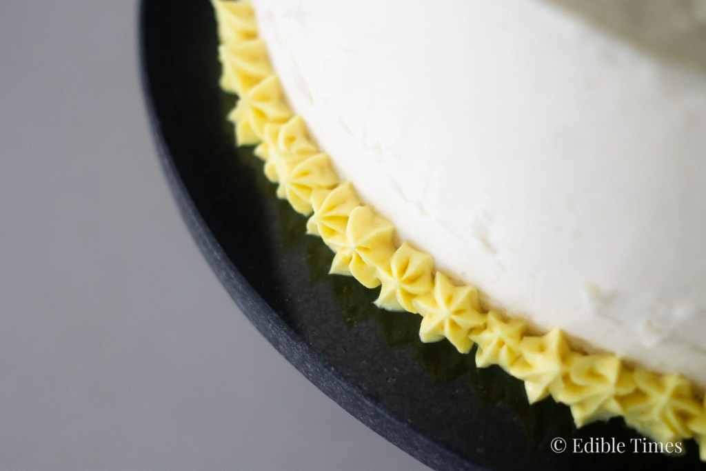 Yellow buttercream stars piped around bottom of cake.