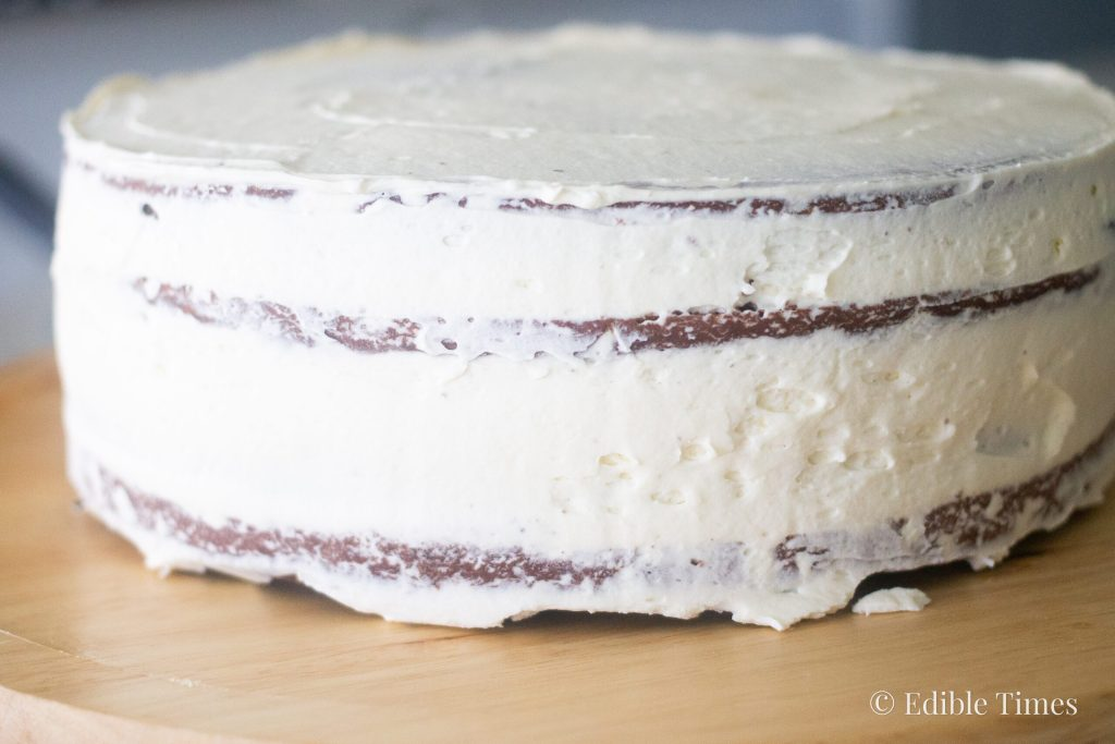 Crumb coat on three-layer chocolate cake.