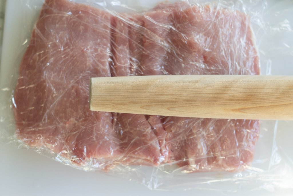 Rolling pin on top of plastic-wrap covered pork loin.