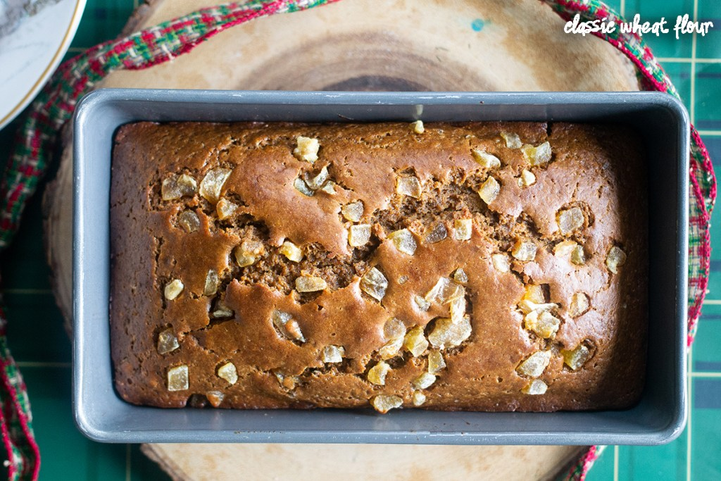Gingerbread loaf still in pan on wooden charger.