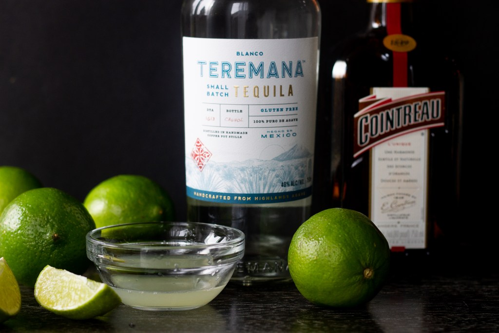 Margarita ingredients on a counter, limes, lime juice, tequila and Cointreau (orange liqueur)