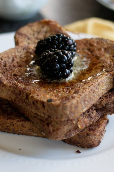 Brioche French toast with keto bread stacked on white plate with berries and melted butter.