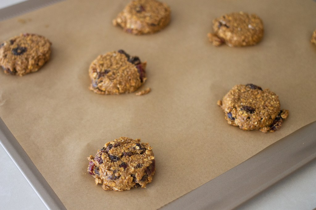 Flattened balls of oatmeal cookie dough on cookie sheet.