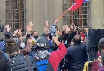 Constituyentes con las manos en Alto intentan impedir el avance del guanaco, en afueras del Congreso en Santiago